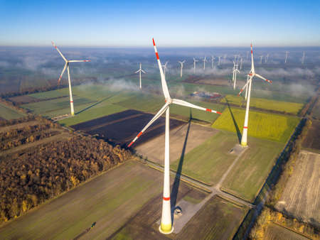 Aerial view of wind energy turbines on windfarm above mist layer on german countryside in the morning sun. Germany Stock fotó