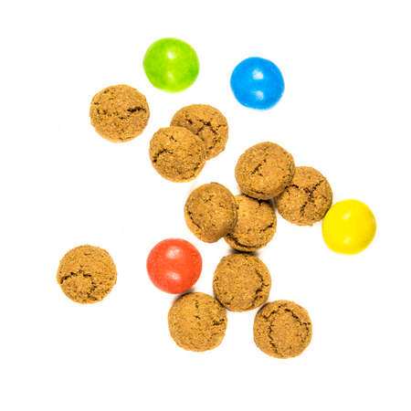 Group of scattered pepernoten cookies and sweets from above on white background for annual Sinterklaas holiday event in the Netherlands on December 5th