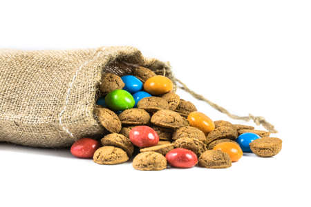 Colorful gingerbread cookies treats in jute bag on white background for annual Sinterklaas holiday event in the Netherlands on December 5th