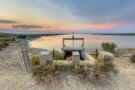 Hydraulic Weir in dam in colorful lagoon under beautiful sunset in Camarque regional nature reserve, Provence Alpes Cote d'Azur, France