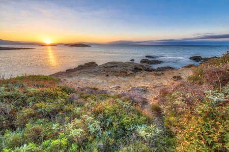Peloponnese coast near Skala at sunrise with rocky shore and coastal vegetation