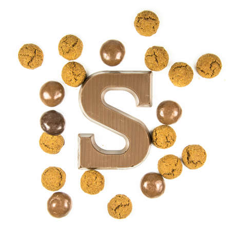 Chocolate letter S with bunch of scattered pepernoten cookies from above on white background for annual Sinterklaas holiday event in the Netherlands on December 5th