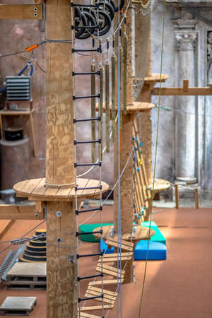 Indoor adventure park with masts, platforms and climbing ropes