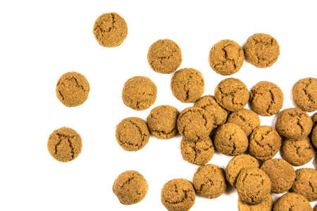 Big Throw of scattered pepernoten cookies from above on white background for annual Sinterklaas holiday event in the Netherlands on December 5th 免版税图像