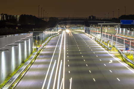 Motorway with entrance of tunnel at night with blurred car lights by long exposure 免版税图像