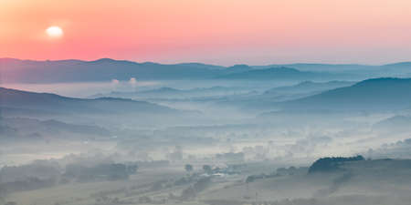 Tuscany hilly landscape scene with early morning haze over village countryside