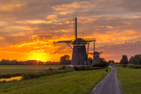 Three historic wooden windmills under orange sunset in dutch polder landscape