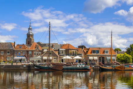 BLOKZIJL, THE NETHERLANDS - JULY 13, 2017: Scenic Harbor in the historic village of Blokzijl on sunny summer day with old flat bottom ships and monumental houses and church, Netherlands