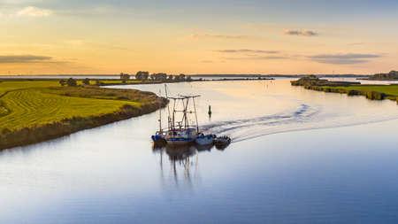 Aerial view of Zwarte Water river near IJsselmeer with fishing ship, Zwartsluis, Overijssel Province, the Netherlands. Landscape scene in nature of Europe.