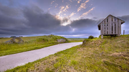 Road passage through old sea dike at sunset under beautiful clouded sky. Usquert, Groningen Province, Netherlands Banque d'images