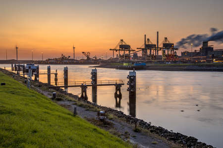 Industrial landscape scene at sunset. Iron ore harbour at steel factory in IJmuiden. The Netherlands.