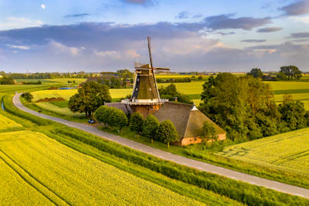 Historic windmill at a farm in agricultural landscape on the countryside of Groningen Province, the Netherlands.