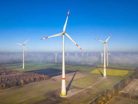 Aerial view of wind turbines in windfarm above mist layer on german countryside in the morning sun. Germany