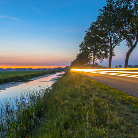 Netherlands open polder landscape with canal and traffic lights on road in open grassland countryside at sunset Zdjęcie Seryjne