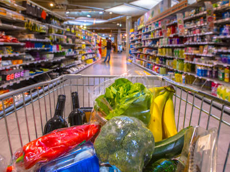 Grocery cart in supermarket filled with food products seen from the customers point of view Banque d'images