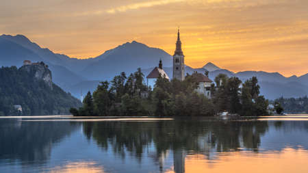 Landmark Lake Bled with St Mary's church and mountains in backdrop under orange morning sky, Slovenia, Europe