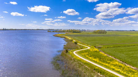 Aerial Springtime scene of dutch river near Boornzwaag. Cycling track on dike meandering throug polder with yellow flowers. Friesland, the Netherlands. Archivio Fotografico
