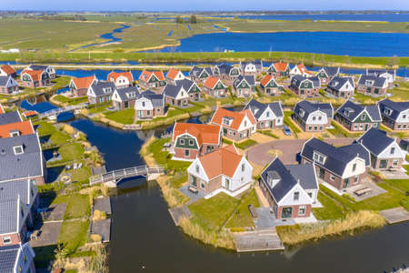 Aerial scene of Resort Poort van Amsterdam is characterized by its unique location. With traditional style chalets and the gently flowing water of the Marker lake just a few metres away from the holiday park.