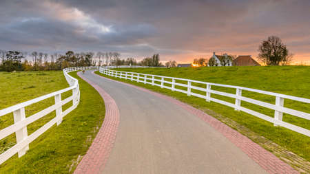 Dutch Countryside landscape with historical houses in evening along a curved road with white fence in the country, Groningen Province, The Netherlands. Landscape scene in nature of Europe. Archivio Fotografico