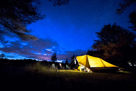 Family tent with rigid steel poles on camping ground under Starry sky with Milky Way