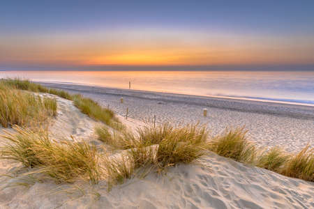 Sunset View over ocean from dune over North Sea and Canal in Ouddorp, Zeeland Province, the Netherlands. Outdoor scene of coast in nature of Europe.
