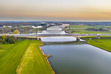 Aerial view of huge lowland river IJssel with highway and railroad bridges through sunset landscape. Zwolle, Overijssel Province, the Netherlands. Drone scene in nature of Europe.