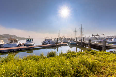 Various ships moored on a wooden quay in harbor in Haringvliet inlet, Zeeland Province the Netherlands.