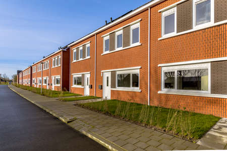 Brand new development of basic public housing in a village in the Netherlands. Neighborhood scene of street with modern suburban terraced houses. Archivio Fotografico