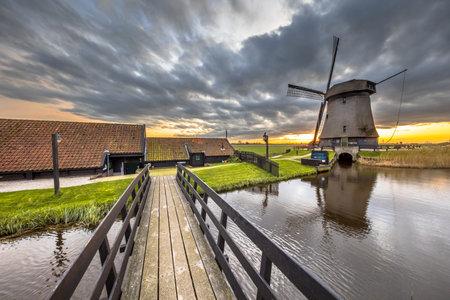 Bridge to Traditional wooden windmill in old agricultural landscape near Schermerhorn, North Holland. Netherlands Archivio Fotografico