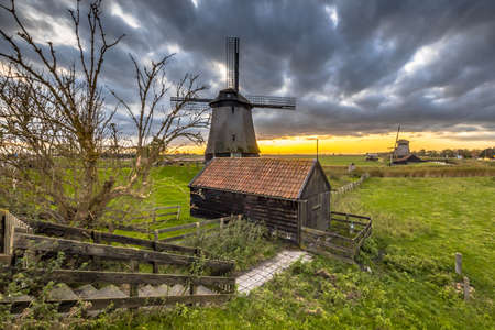 Traditional wooden windmill with shack in old agricultural landscape near Schermerhorn, North Holland. Netherlands