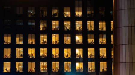 Esterno dell'edificio per uffici di notte con luci interne accese. Uffici vuoti.