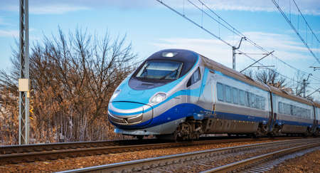 Modern high speed aerodynamic streamlined electric train passing by.