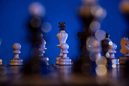 Chess board with chess pieces on blue background. Concept of business ideas and competition and strategy ideas. Figures close up.