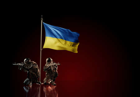 Concept of military conflict with soldier statues and waving national flag of Ukraine. Illustration of coup idea. Two guards defending the symbol of country against red wall