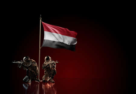Concept of military conflict with soldier statues and waving national flag of Yemen. Illustration of coup idea. Two guards defending the symbol of country against red wall