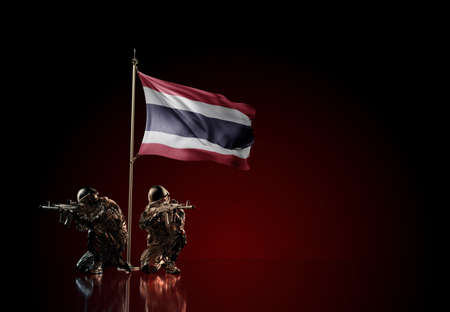 Concept of military conflict with soldier statues and waving national flag of Thailand. Illustration of coup idea. Two guards defending the symbol of country against red wall