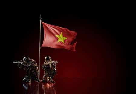 Concept of military conflict with soldier statues and waving national flag of Vietnam. Illustration of coup idea. Two guards defending the symbol of country against red wall