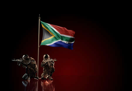 Concept of military conflict with soldier statues and waving national flag of South Africa. Illustration of coup idea. Two guards defending the symbol of country against red wall Reklamní fotografie