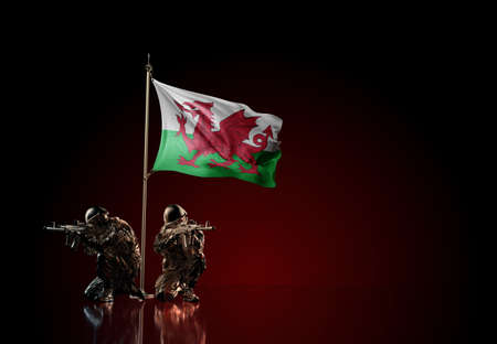 Concept of military conflict with soldier statues and waving national flag of Wales. Illustration of coup idea. Two guards defending the symbol of country against red wall Reklamní fotografie