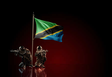 Concept of military conflict with soldier statues and waving national flag of Tanzania. Illustration of coup idea. Two guards defending the symbol of country against red wall