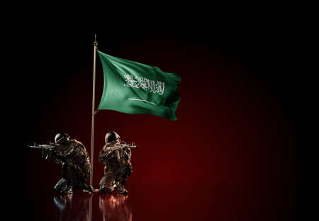 Concept of military conflict with soldier statues and waving national flag of Saudi Arabia. Illustration of coup idea. Two guards defending the symbol of country against red wall