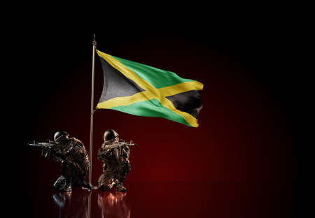 Concept of military conflict with soldier statues and waving national flag of Jamaica. Illustration of coup idea. Two guards defending the symbol of country against red wall Reklamní fotografie