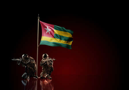 Concept of military conflict with soldier statues and waving national flag of Togo. Illustration of coup idea. Two guards defending the symbol of country against red wall
