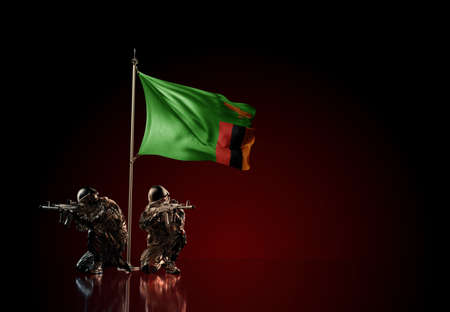 Concept of military conflict with soldier statues and waving national flag of Zambia. Illustration of coup idea. Two guards defending the symbol of country against red wall