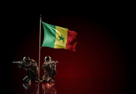 Concept of military conflict with soldier statues and waving national flag of Senegal. Illustration of coup idea. Two guards defending the symbol of country against red wall Reklamní fotografie