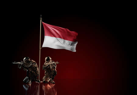 Concept of military conflict with soldier statues and waving national flag of Monaco. Illustration of coup idea. Two guards defending the symbol of country against red wall Reklamní fotografie