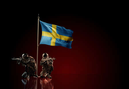 Concept of military conflict with soldier statues and waving national flag of Sweden. Illustration of coup idea. Two guards defending the symbol of country against red wall
