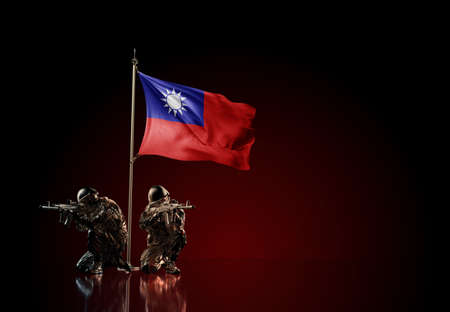 Concept of military conflict with soldier statues and waving national flag of Taiwan. Illustration of coup idea. Two guards defending the symbol of country against red wall Reklamní fotografie