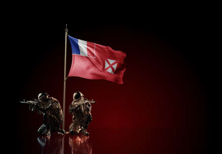 Concept of military conflict with soldier statues and waving national flag of Wallis and Futuna. Illustration of coup idea. Two guards defending the symbol of country against red wall Reklamní fotografie