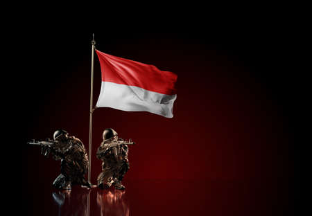 Concept of military conflict with soldier statues and waving national flag of Indonesia. Illustration of coup idea. Two guards defending the symbol of country against red wall Reklamní fotografie